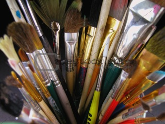 Old paint brushes standing in clear glass cup