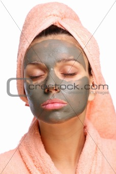 Close face of young woman with a mud mask on it. Isolated on a white background.
