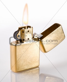 Flaming golden lighter on a white background