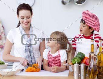 Mother and children cutting peppers in kitchen