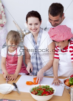 Happy family preparing a salad in kitchen