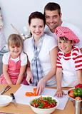Young family cutting vegetables in kitchen