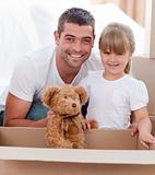 Little girl and her father  unpacking boxes