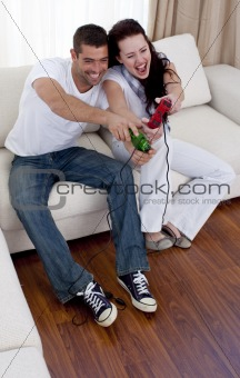Couple having fun playing video games in living-room