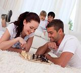 Smiling couple playing chess on floor in living-room