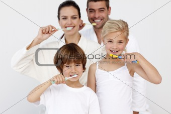 Portrait of family cleaning their teeth in bathroom