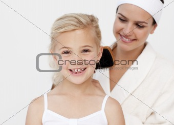 Beautiful mother doing daughter's hair