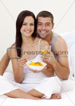 Couple eating fruit and orange juice in bed