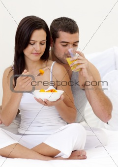 Couple eating fruit and drinking orange juice in bed