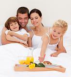 Happy family having breakfast in bedroom