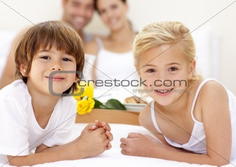 Portrait of children in bed with their parents