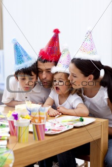 Little girl blowing out candles in her birthday's day with famil