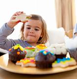 Happy little girl eating confectionery at home