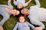 Little girl lying in a park with her parents and brother
