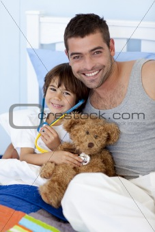 Happy father and son playing doctors in bed with a teddy bear