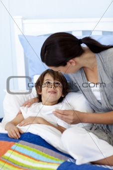 Mother giving her son lying in bed syrup