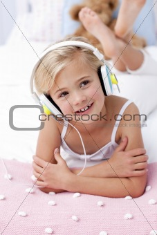 Little girl listening to the music in bed with headphones