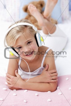 Portrait of little girl lying in bed listening to the music