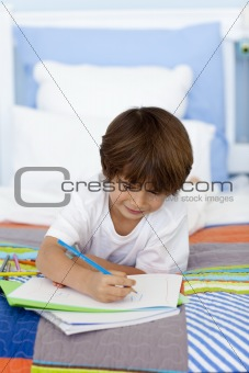 Little boy drawing in bed