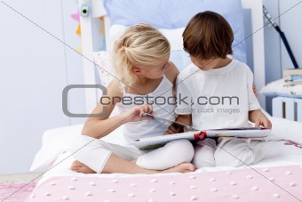 Brother and sister reading a book in bed