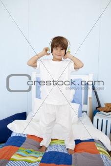 Little boy with headphones on dancing in bedroom