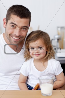 Dad and little girl eating biscuits with milk