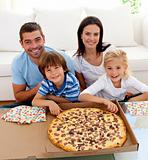 Family eating pizza on sofa