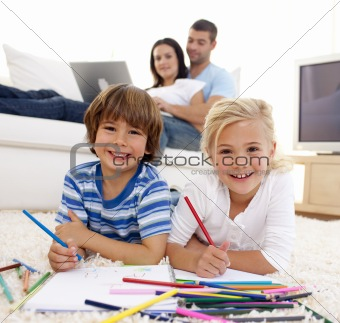 Smiling brother and sister painting in living-room