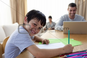 Boy painting and father using a laptop and mother reading