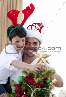 Dad and boy decorating Christmas tree