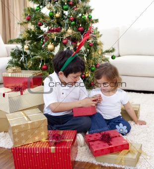 Happy brother and sister looking at Christmas gifts