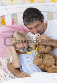 Daughter and father playing doctors with a teddy bear