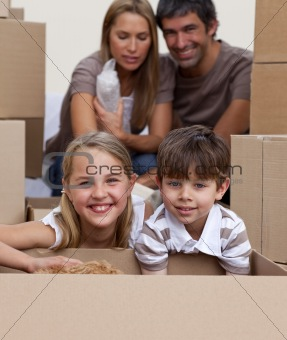 Portrait of children unpacking boxes with their parents