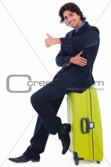 Corporate man sitting above the luggage showing thumbsup