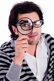 young man looking stright with a magnifying glass