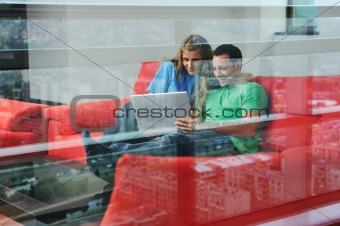 happy couple have fun and work on laptop at home on red sofa