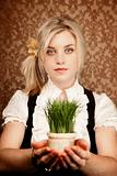 Pretty young woman with pot of grass