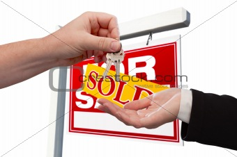 Agent Handing Over the Key to a New Home with Real Estate Sign in the Background Isolated on White.
