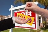 Agent Handing Over the Key to a New Home with Real Estate Sign and House in the Background.