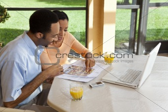 African American Couple Using Laptop Computer To Surf The Intern