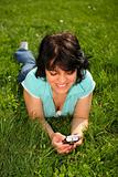 Woman lying on the lawn using mobile