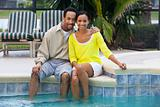 Happy African American Couple Sitting Outside Next To Swimming P