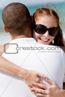 Portrait of pretty woman holding her husband while at beach