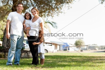 Mom holding one of the daughter and lifting the other kid with her husband