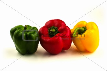 Three sweet peppers in a line on white