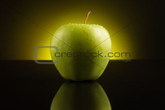 Green apple with drops on yellow background