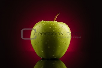 Green apple with drops on red background