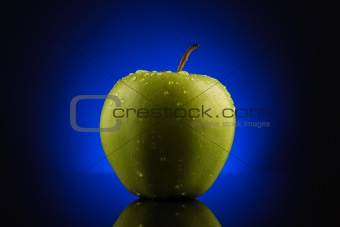Green apple with drops on blue background