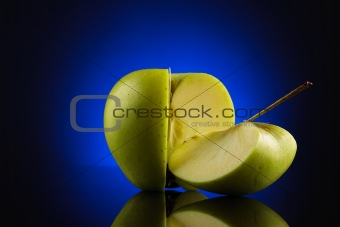 Green quarter and three quarters apple with on blue background