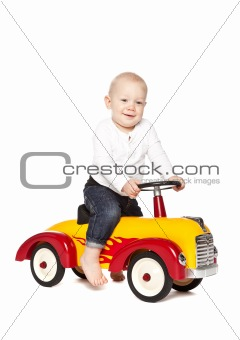 Boy riding his toycar